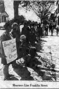"People lining the sidewalk on Franklin Street. One holds a sign reading ""Brotherhood and Human Dignity."" Caption reads ""Mourners Line Franklin Street."""