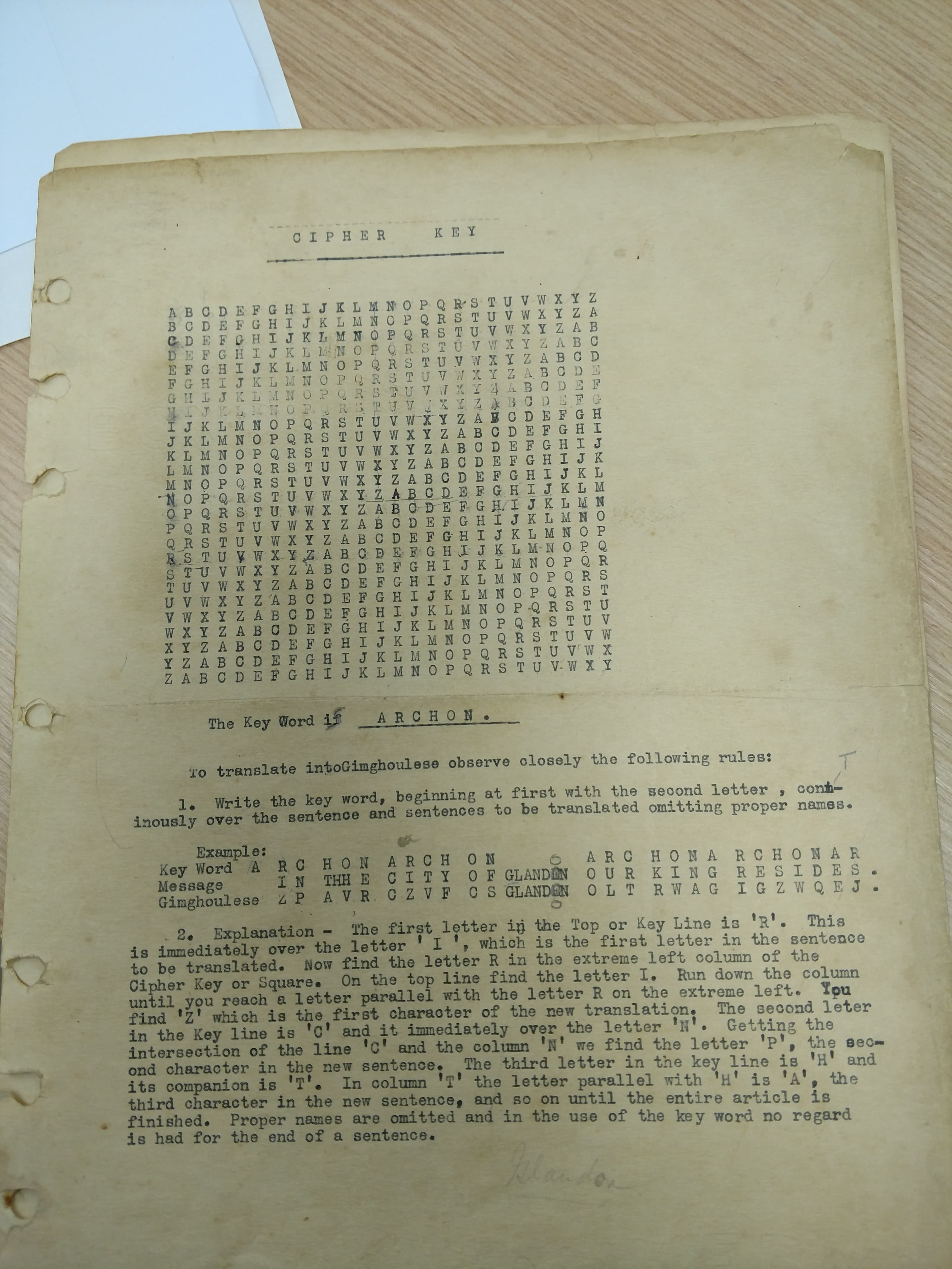 A yellowed page featuring a square of letters and instructions for deciphering a code.