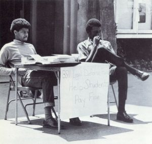 "Two young black men sit at a table outside on the campus of UNC Chapel Hill. The table has sign that reads"" BSM Legal Defense Fund/Help Students Pay Fine."""