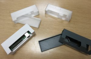 Shows four 3-d printed cases. Three attempts and the final case.
