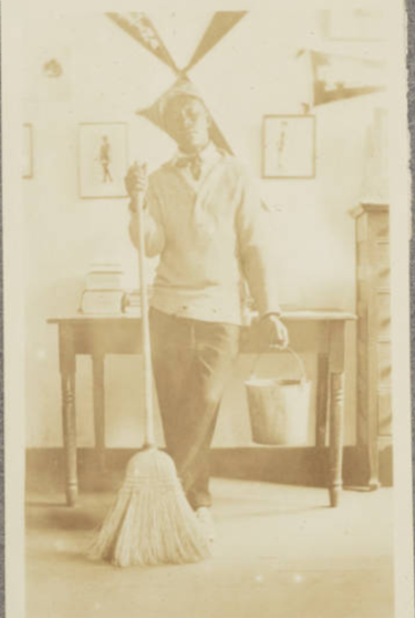 Photo of a young man holding a bucket and broom